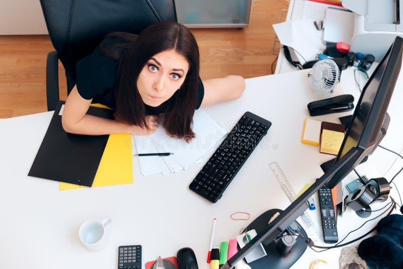 滑稽的女孩坐超时运转杂乱的书桌 免版税库存照片