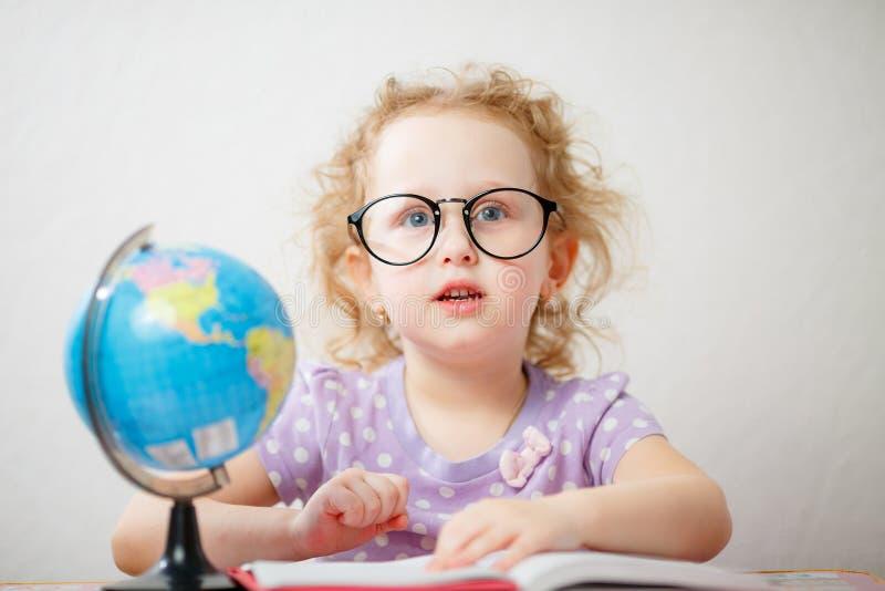 滑稽的女孩接近的照片画象戴眼镜的 她通过在桌上的书生叶是地球 免版税库存图片