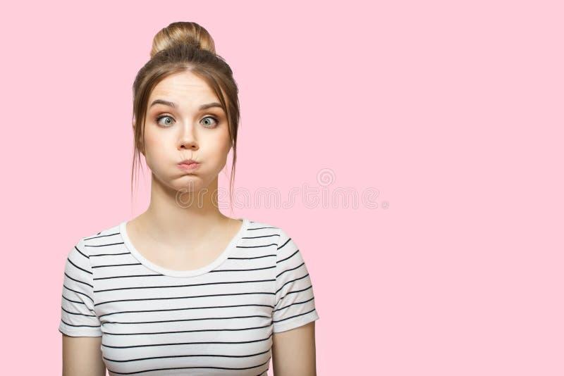 滑稽的妇女吹的面颊 桃红色背景 免版税库存图片