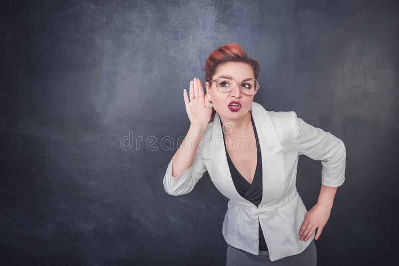 滑稽的妇女在黑板背景窃听 图库摄影