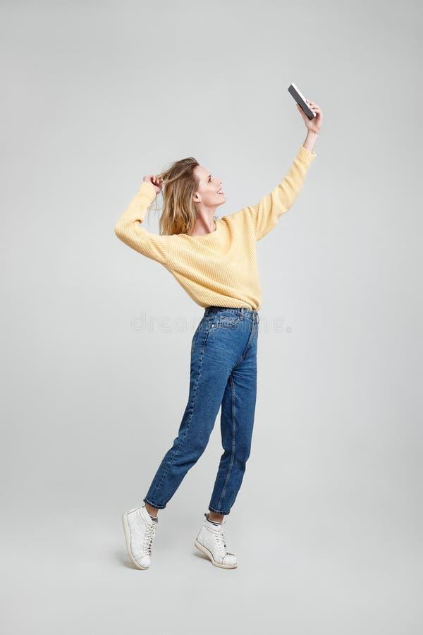 滑稽的妇女的全长图象做selfie的便服的在智能手机,当握她的在灰色背景时的头发 ? 免版税库存照片