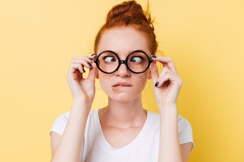 滑稽的姜妇女的特写镜头图片显示鬼脸的eyeglasess的 库存照片