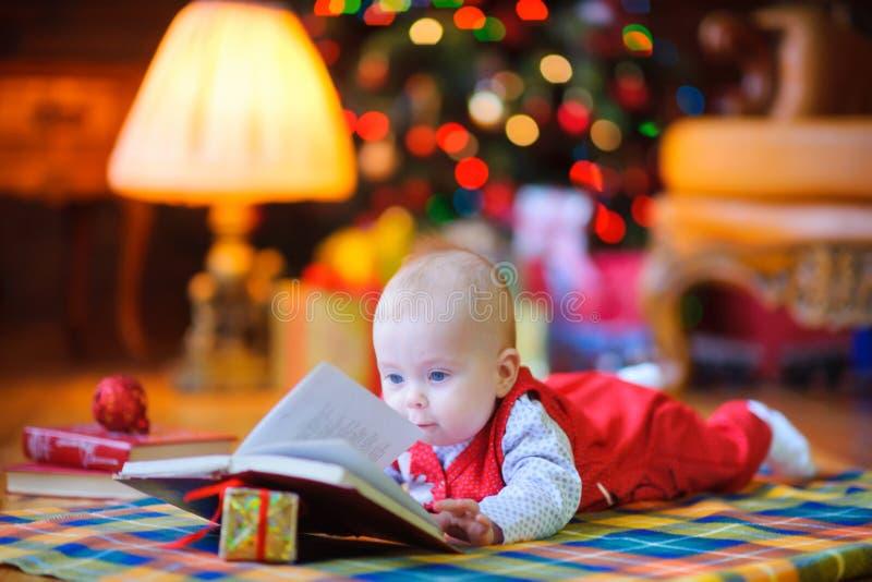 滑稽的孩子在地板上说谎在圣诞树附近 图库摄影
