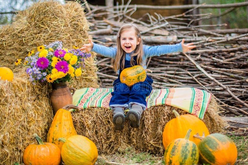 滑稽的孩子在干草背景中用南瓜 免版税库存照片