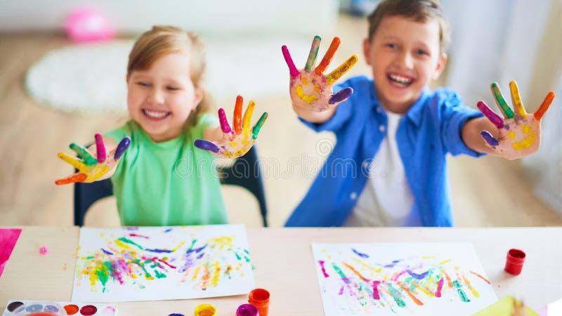 滑稽的孩子显示他们的棕榈被绘的油漆 创造性的类美术 两个孩子男孩和女孩笑 有选择性聚焦 库存照片