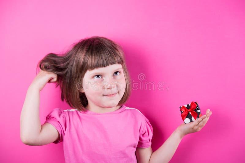 滑稽的小女孩在她的手上的拿着相当被察觉的礼物盒在明亮的桃红色背景 图库摄影