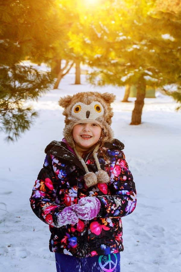 滑稽的小女孩获得乐趣在美丽的冬天公园在降雪期间 库存照片