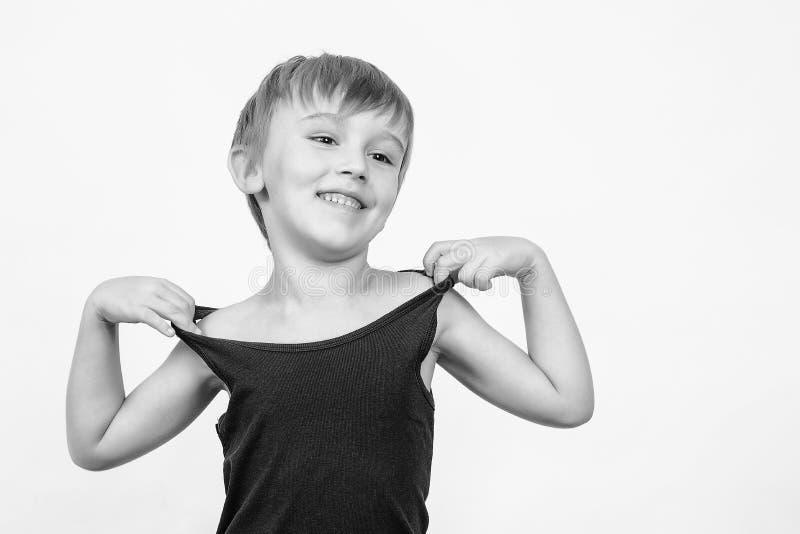 滑稽的小男孩画象在白色背景的 看愉快的孩子微笑和在旁边 复制空间 黑无袖衫的孩子 库存图片