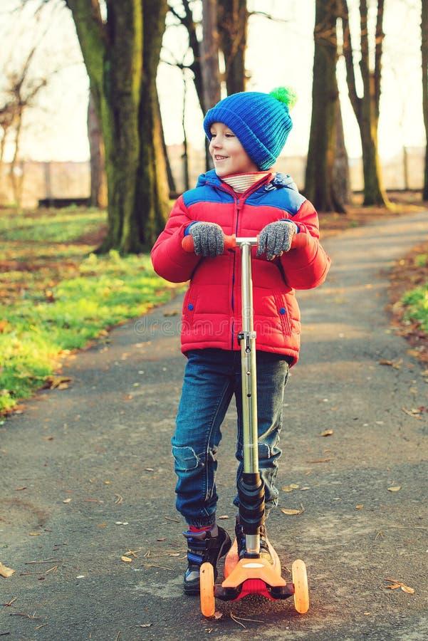 滑稽的小男孩骑马滑行车在城市公园在冷的秋天 r 秋天和冬天时尚 愉快儿童使用 免版税库存照片