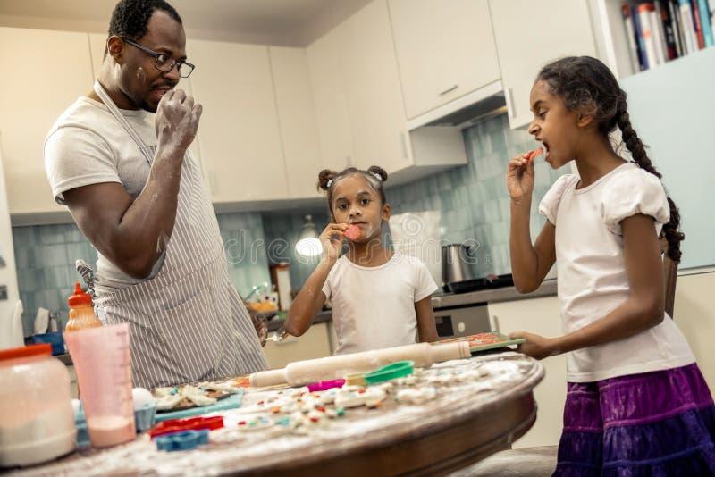 滑稽的尝试一些蒜味咸腊肠的女儿和父亲,当烹调比萨时 库存图片