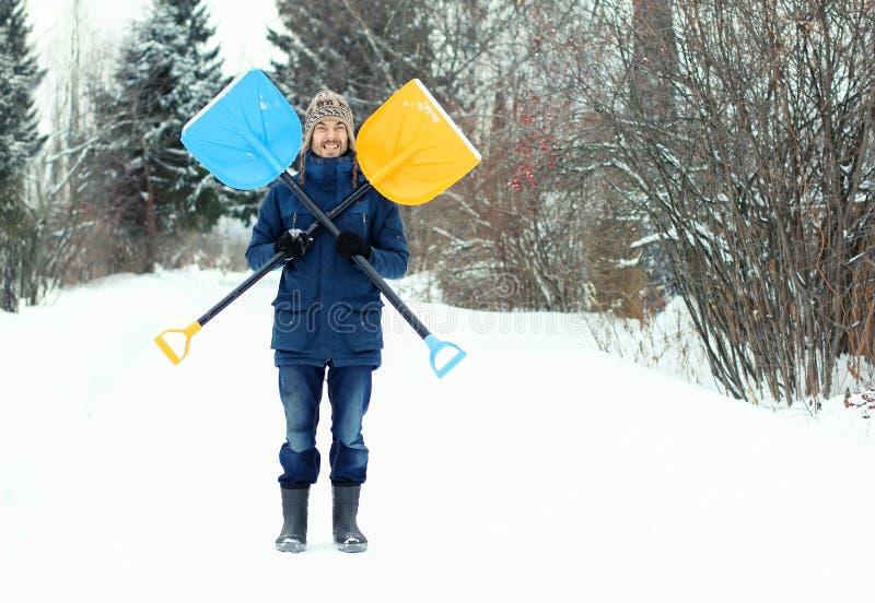 滑稽的年轻人拿着两把雪铁锹,形成海盗旗的标志 冬天季节性概念 图库摄影