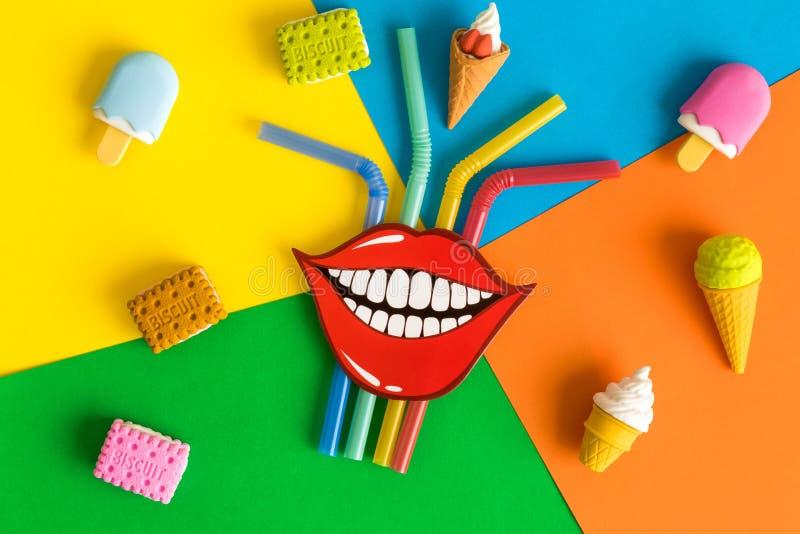 滑稽的微笑平的位置与吸管、冰淇淋和饼干的在多彩多姿的背景摘要 免版税库存图片