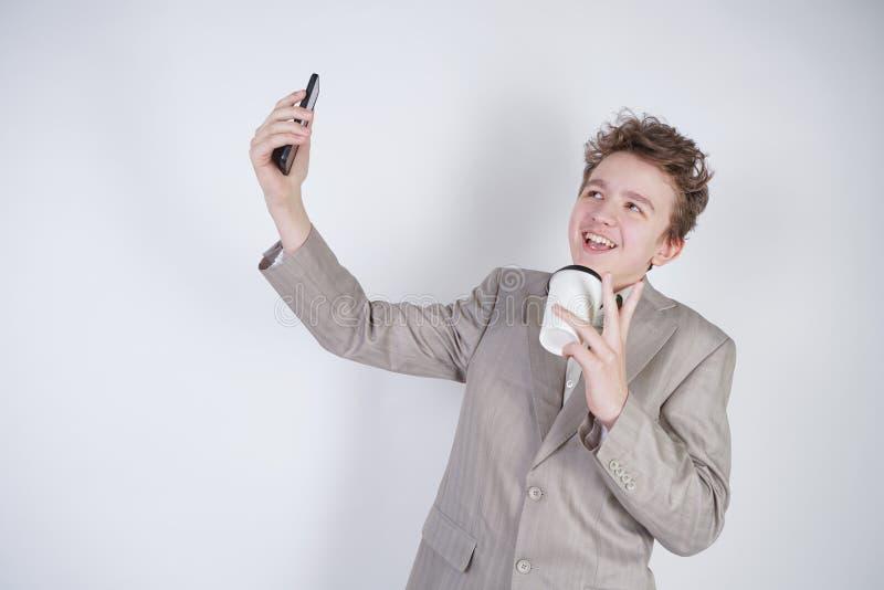 滑稽的微笑的少年获得与智能手机的乐趣在他的手 佩带与纸杯的青少年的男孩灰色西装身分cof 图库摄影