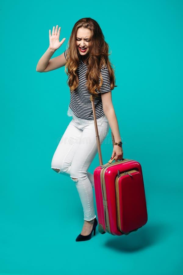 滑稽的情感妇女藏品和跳舞与桃红色旅行包 免版税库存照片
