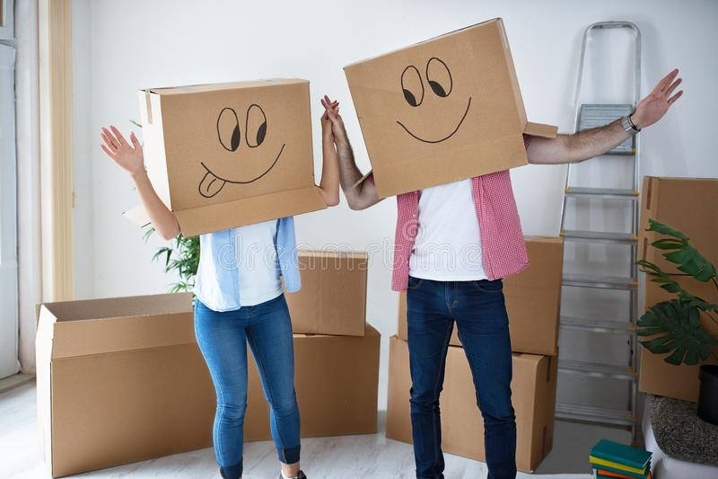 滑稽的愉快的夫妇坐地板佩带的纸板箱 免版税库存图片