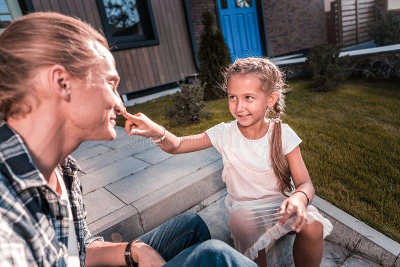 滑稽的时髦的黑眼睛的接触她的父亲的鼻子的女孩佩带的白色礼服 免版税库存图片