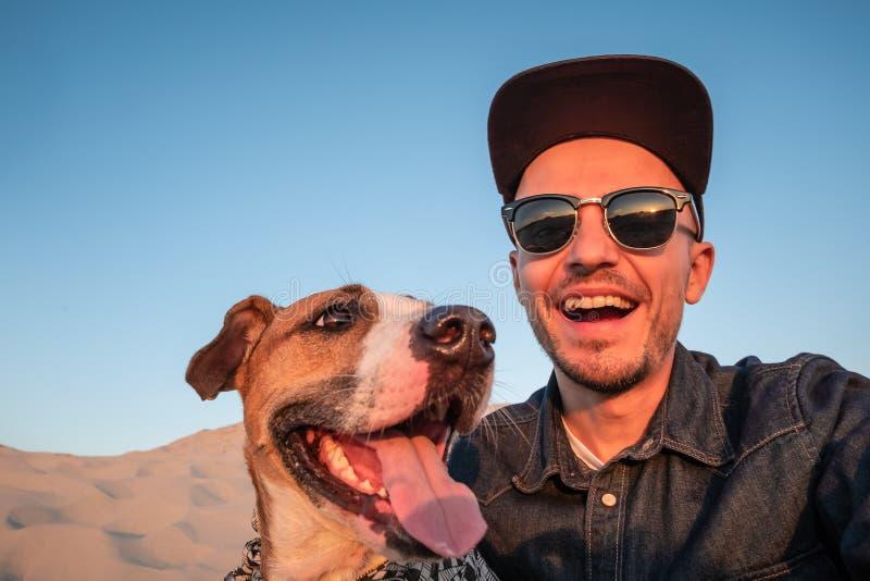 滑稽的最好的朋友概念:采取与狗的人一selfie Happ 库存照片