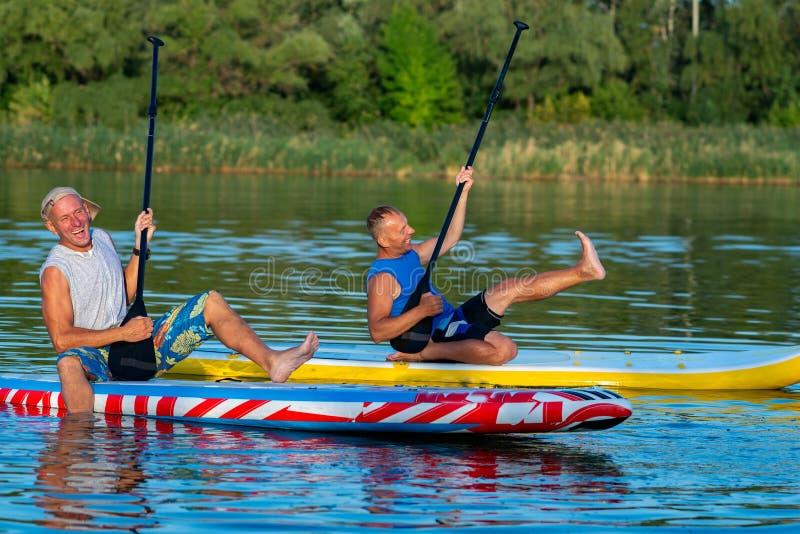 滑稽的朋友,获得一口的冲浪者笑和乐趣 免版税库存照片