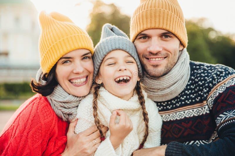 滑稽的极度高兴的小孩子笑有与她的父母的美妙的时间 富感情的父母在的他们的小女儿附近站立 免版税库存照片