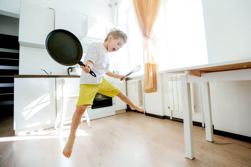 滑稽的欧洲小男孩厨师跳舞,周末愉快,男孩要做薄煎饼,但是煎锅是太快乐的,他 免版税图库摄影