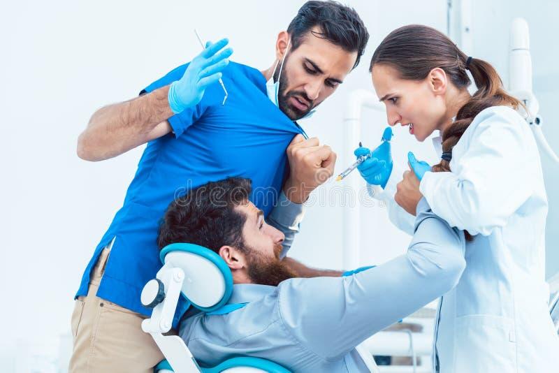 滑稽的牙医或行动的牙医疯狂在他的助理前面 免版税库存图片