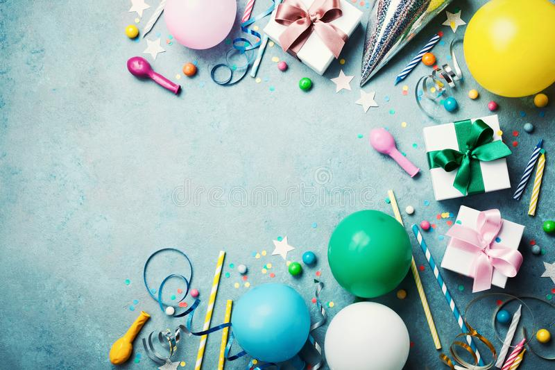 滑稽的生日聚会背景 五颜六色的气球、礼物盒、五彩纸屑、糖果和飘带在绿松石台式视图 平的位置 图库摄影