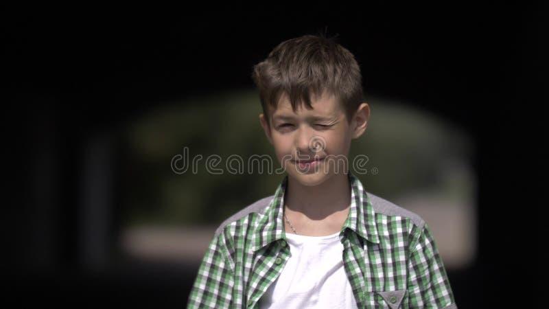 滑稽的男孩从太阳的神色到照相机里和半眯着的眼睛 免版税库存照片