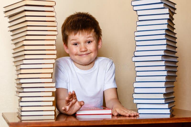 滑稽的男孩和堆书 快乐的孩子是第一辆平地机 免版税库存图片