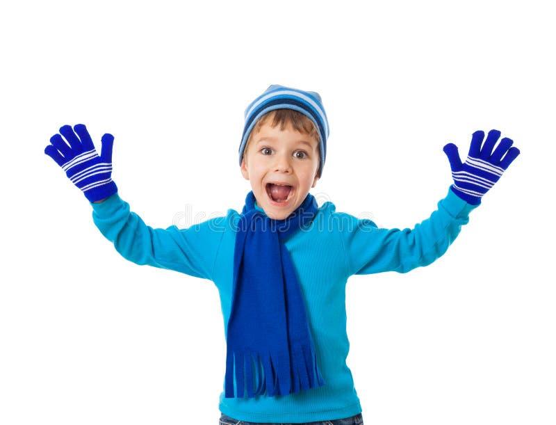 滑稽的男孩在冬天穿衣与问候手标志 免版税库存照片