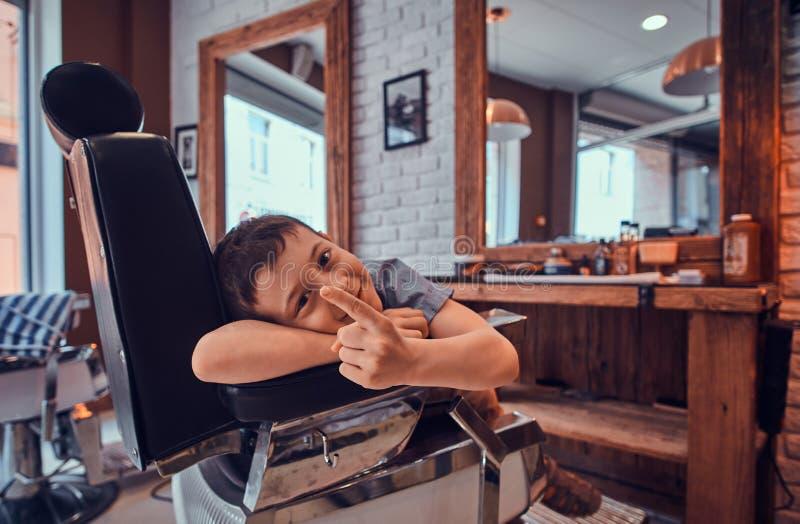 滑稽的男孩显示他的手指,当等待美发师在繁忙的理发店时 免版税图库摄影