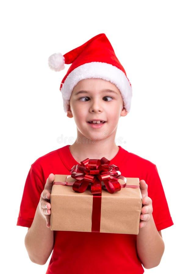 滑稽的男孩,半眯着眼睛看的眼睛,在他的头的圣诞老人帽子,有礼物盒的在手上 概念:圣诞节或新年快乐 免版税库存图片
