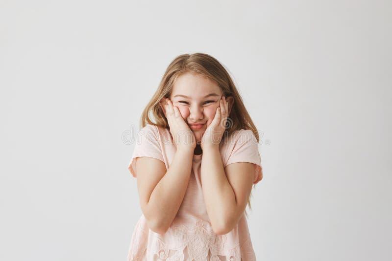 滑稽的白肤金发的女孩画象桃红色礼服的,紧压面孔用手,做防止母亲的傻的面孔采取 免版税库存照片
