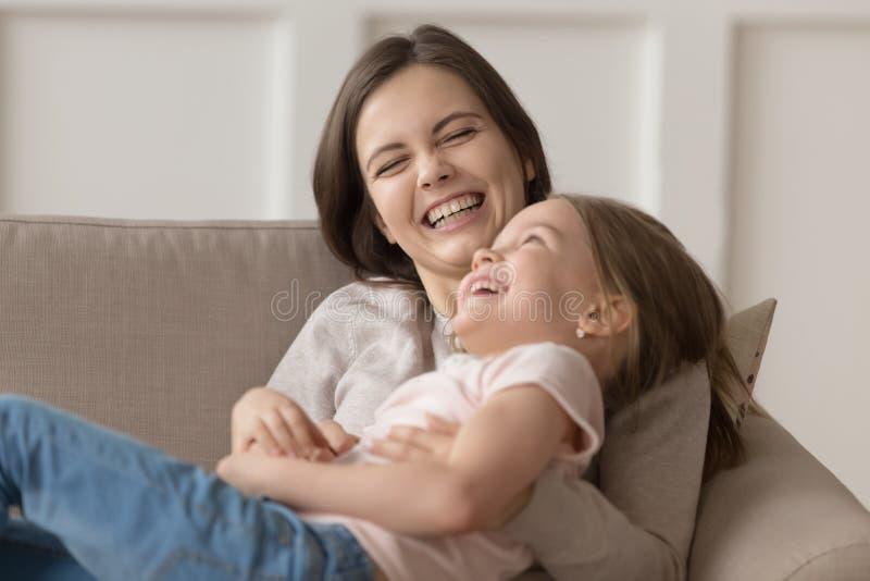滑稽的笑的母亲发痒说谎在长沙发的小女儿家庭 库存照片