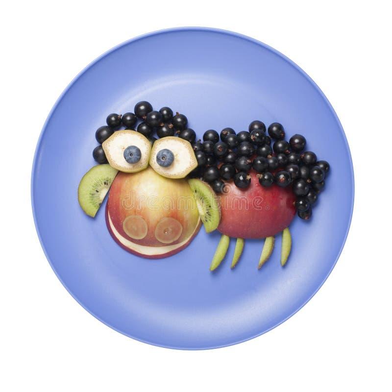 滑稽的绵羊做用新鲜水果在板材 免版税图库摄影