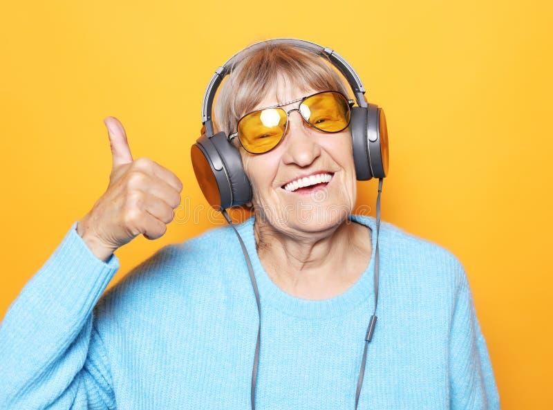 滑稽的老妇人听的音乐和显示赞许 免版税库存图片