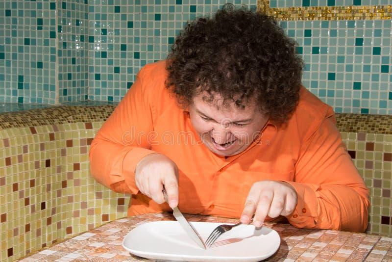 滑稽的肥胖人和一块空的板材 饮食和一种健康生活方式 免版税图库摄影
