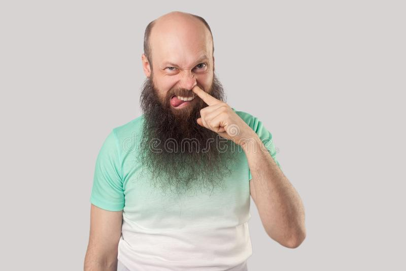 滑稽的肮脏的中部画象变老了有长的胡子的秃头人在与手指的浅绿色的T恤杉身分钻井在他的鼻子, 免版税库存照片