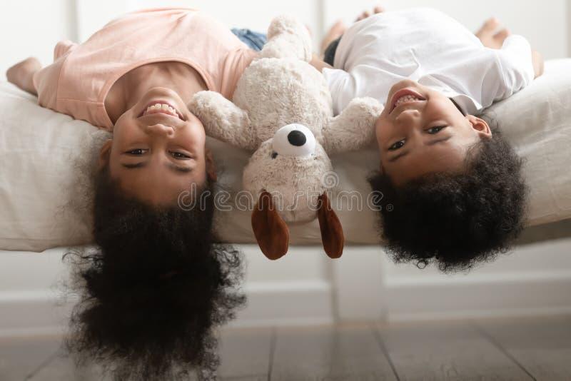 滑稽的说谎颠倒在床上的小男孩和女孩 库存图片