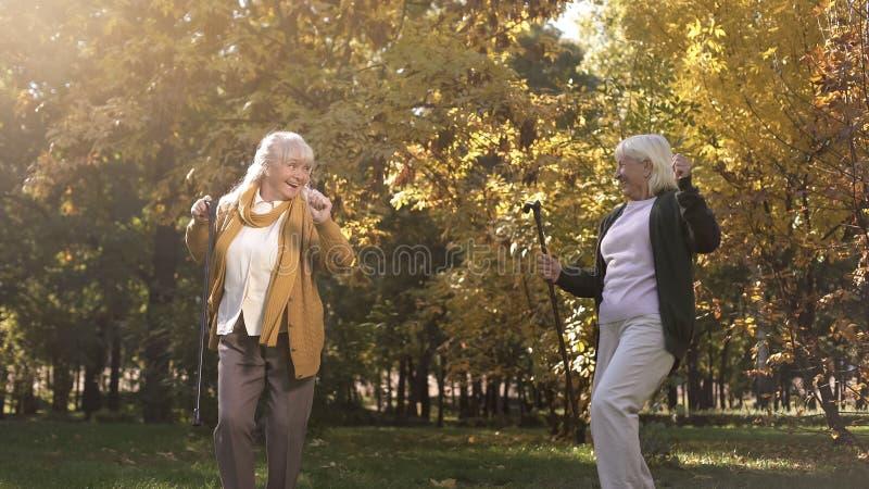滑稽的资深妇女享受天气,跳舞和获得乐趣在温暖的秋天公园 免版税库存图片