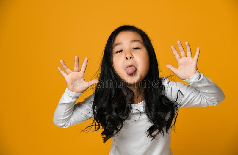 滑稽的逗人喜爱的矮小的亚裔女孩显示舌头 库存图片