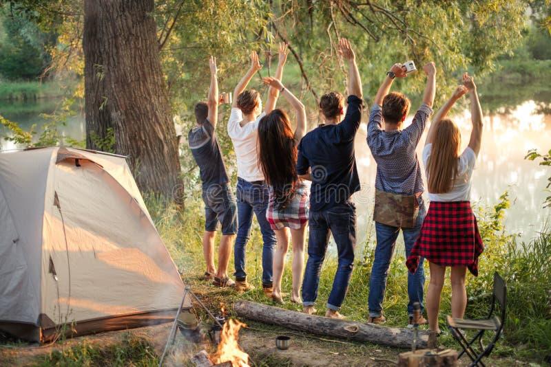 滑稽的青年人遇见他们的朋友,当站立在河时河岸  免版税库存图片
