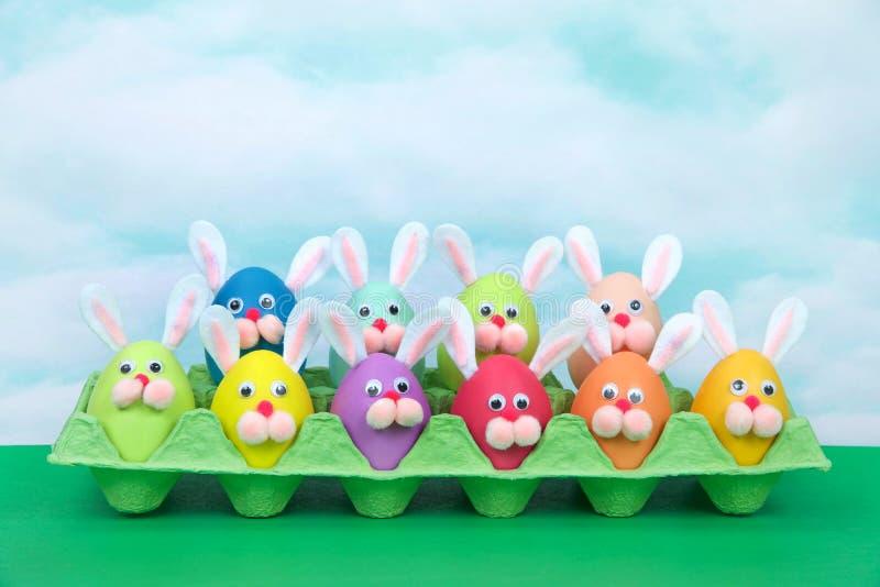 滑稽的面孔复活节兔子在蛋纸盒选材台蓝天怂恿 免版税库存图片