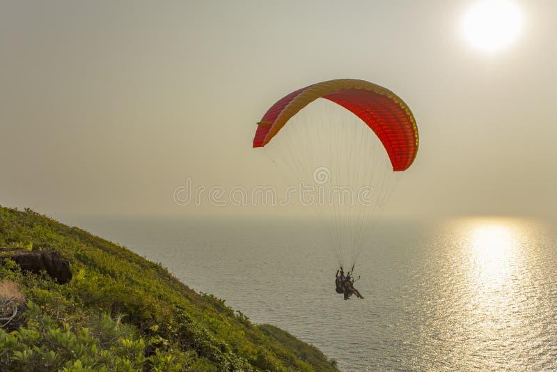 滑翔伞一前一后在一个红黄色降伞的飞越有太阳道路的海洋在 免版税图库摄影