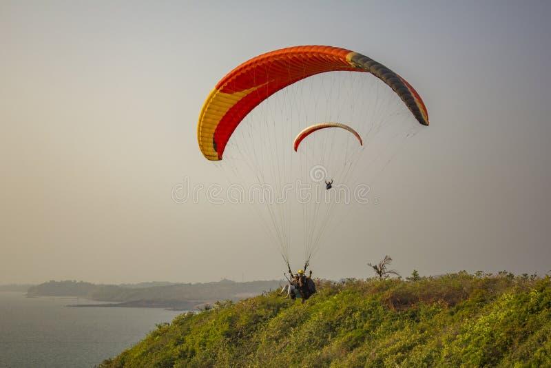 滑翔伞一前一后在一次黄色红色降伞飞行的在海和青山在 免版税库存照片