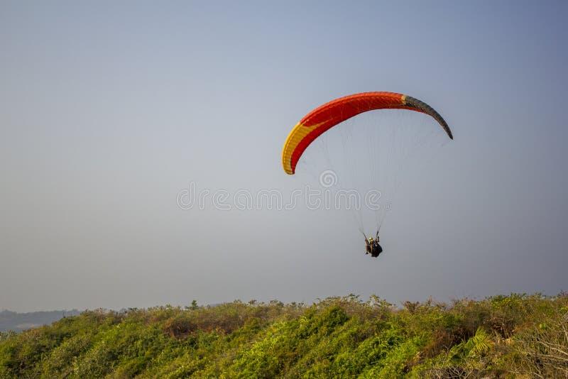 滑翔伞一前一后在一次黄色红色黑降伞飞行的在反对干净的灰色的绿草 免版税图库摄影
