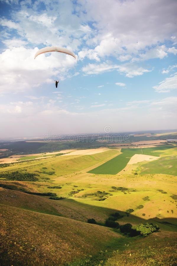 滑翔伞在一套茧衣服的天空飞行在白种人乡下的一个滑翔伞有小山和山的 库存照片