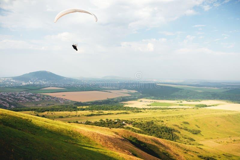 滑翔伞在一套茧衣服的天空飞行在白种人乡下的一个滑翔伞有小山和山的 免版税图库摄影