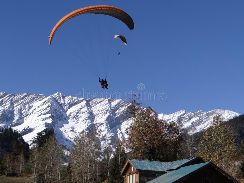 滑翔伞在印度享受他的在积雪的山脉的乘驾 库存图片