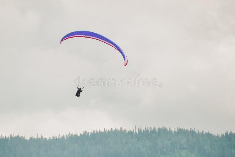 滑翔伞是飞行滑翔伞消遣和竞争冒险体育:轻量级选手,自由飞行,脚发射了 免版税库存图片