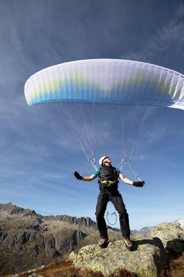 滑翔伞飞行员在岩石站立并且在湖Grimsel附近平衡他的在他的头上的滑翔伞在瑞士阿尔卑斯山脉 免版税库存图片